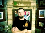 Ben Wurst, owner/founder of reclaimed LLC, stands in front of his display.